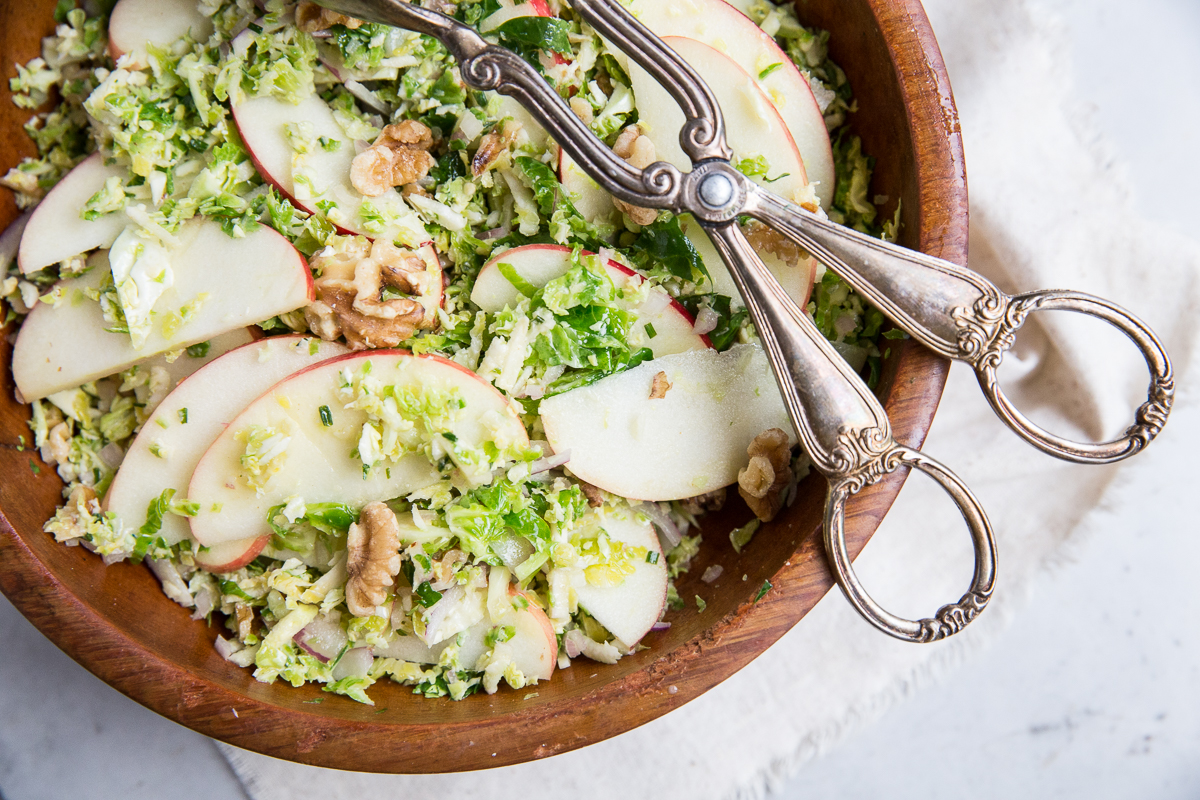 Raw shredded Brussels Sprouts make a great base for this flavorful salad tossed with a walnut dijon vinaigrette.