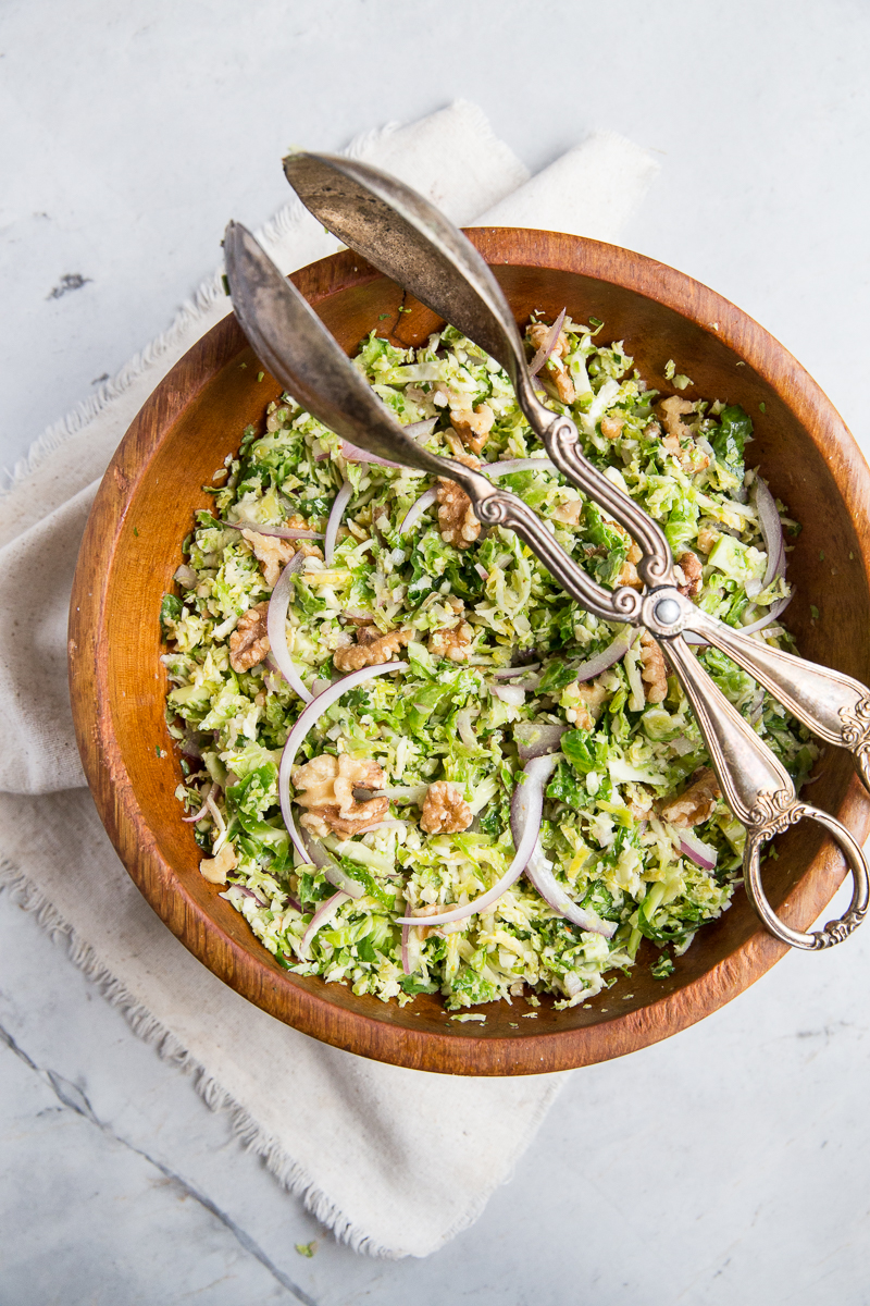 This raw Shredded Brussels Sprout Salad Recipe is a crowd pleaser for holiday gatherings or to accompany a wintery stew or casserole.